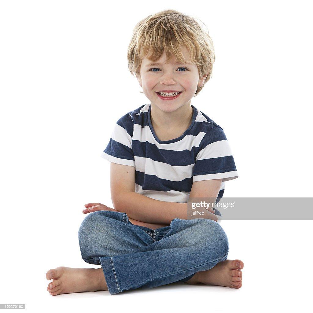 Small boy sitting crossed legged smiling on white : Stock Photo
