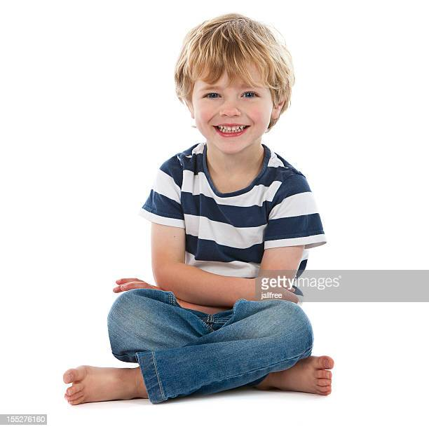 Small boy sitting crossed legged smiling on white