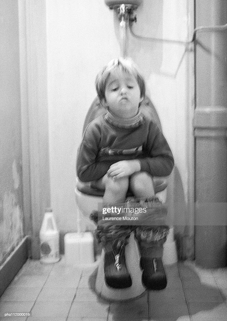 Small boy sitting on the toilet, b&w : Bildbanksbilder