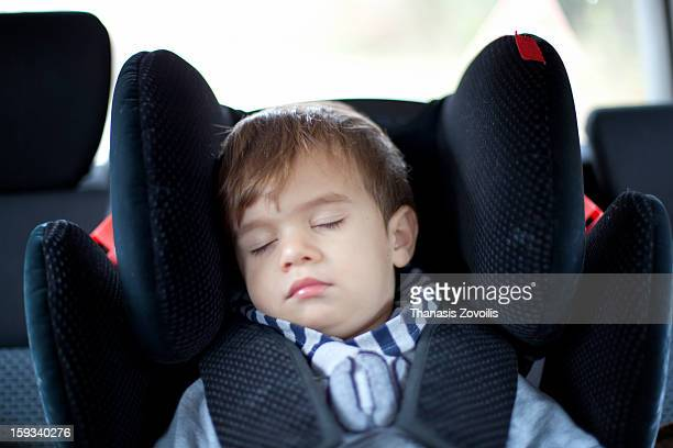 Small boy sleeping in a car