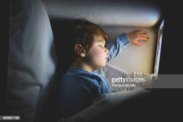 Small boy sleeping in front of a tablet
