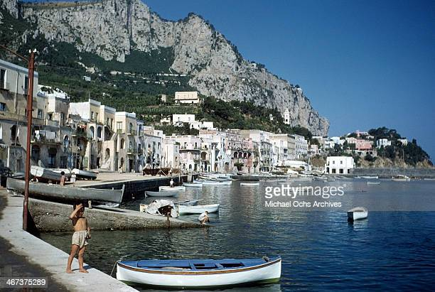 A small boy stands next to a boat in Capri Italy