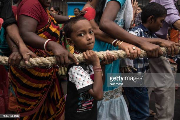 A small boy too is pulling the rope of the chariot with his parents to seek the blessings of lord jagannath during rath yatra in Kolkata India on...