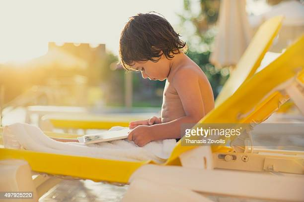 Small boy using a digital tablet neat the pool