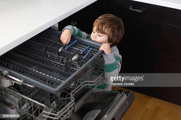 Small boy using a dish machine