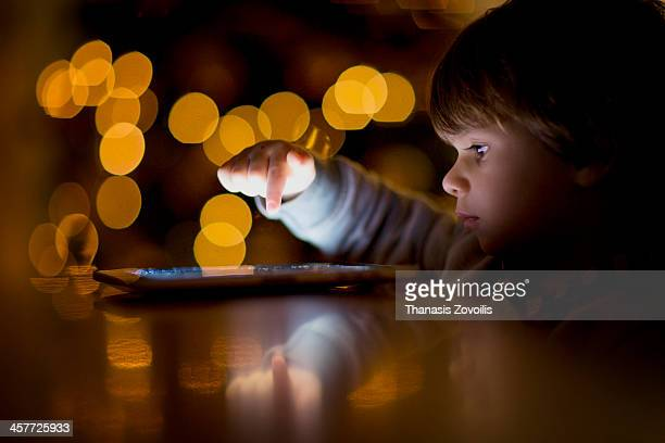 Small boy using a tablet in the dark