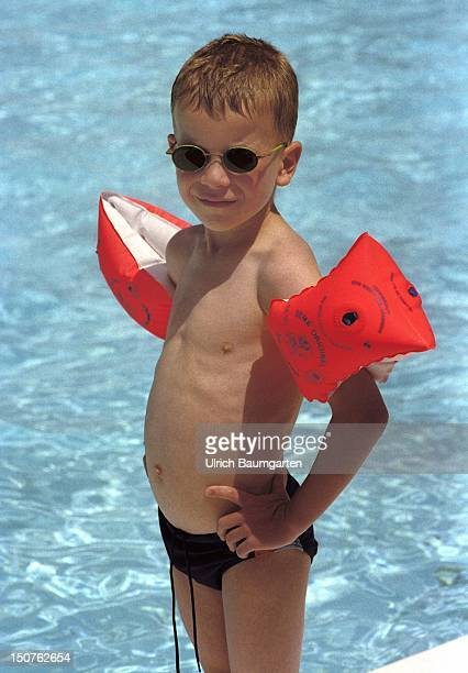 Small boy wearing swimming trunks sunglasses and water wings stands in the sun at a swimming pool