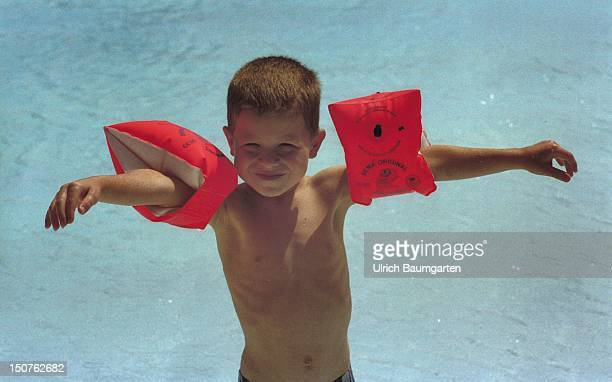 Small boy wearing water wings and stands in the sun at a swimming pool