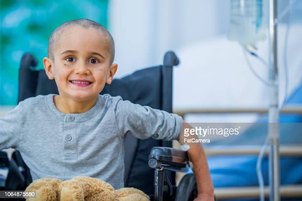 small boy with cancer in wheelchair - cancer illness stock pictures, royalty-free photos & images