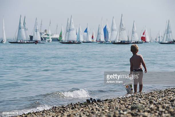 Small boy with his bucket stands in the surf on the beach watching as sailing yachts race against each other during Cowes Week on 5 August 1995 off...