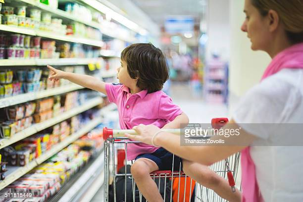 Small boy with his mother in a super market