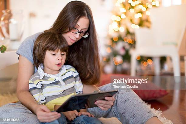 Small boy with his mother using a digital tablet
