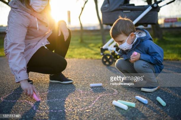 small boy with mother and baby in pram with face mask outdoors, chalk drawing. - mittlerer teil stock-fotos und bilder