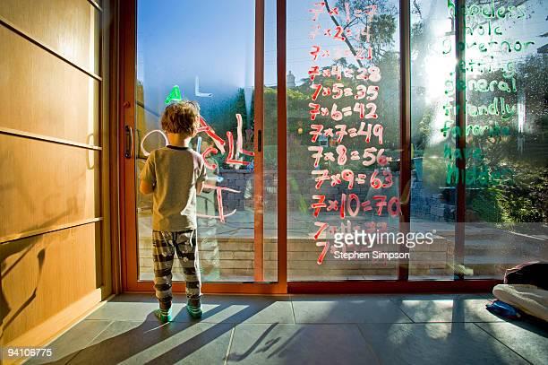 small boy writing on window with glass chalk
