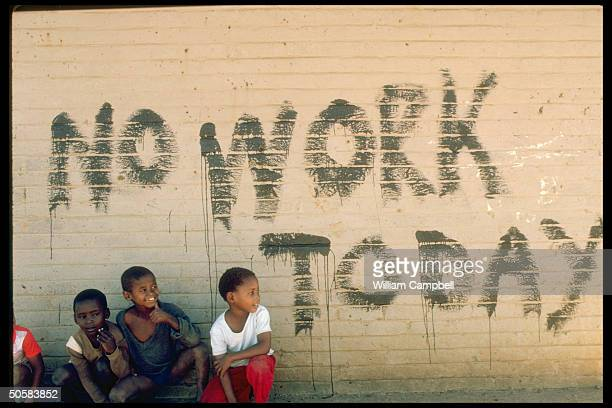 Small boys by NO WORK TODAY graffiti during disturbances marking 25th anniv of killing of 69 blacks by police