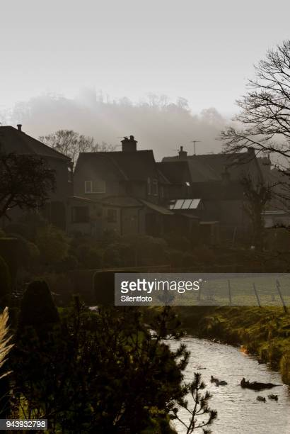a small brook runs behind houses beneath ruins of peveril castle, castleton - peveril castle stock pictures, royalty-free photos & images