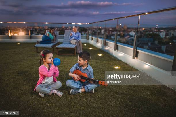 small brother and sister having fun on a penthouse balcony by night. - penthouse girls stock pictures, royalty-free photos & images