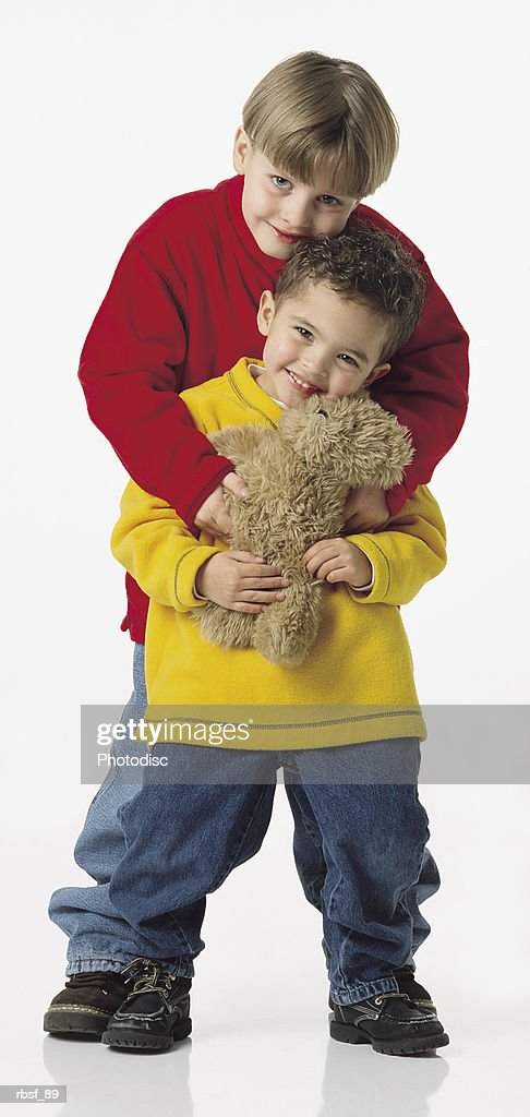 small brothers hold each other with the older brother behind the younger one holding his teddy bear : Foto de stock