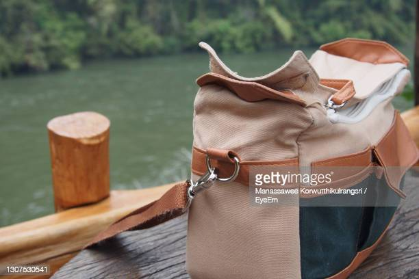 a small brown bag on the table near the river. jungle / adventure theme - evening bag stock pictures, royalty-free photos & images