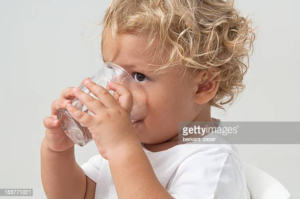 Small brown eyed boy with blonde hair drinking from glass