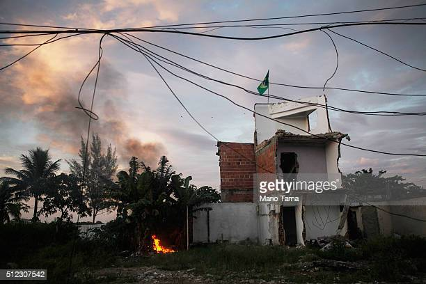 A small brush fire burns at dawn in front of a partially demolished home with a Brazilian flag atop in the mostly demolished Vila Autodromo favela...
