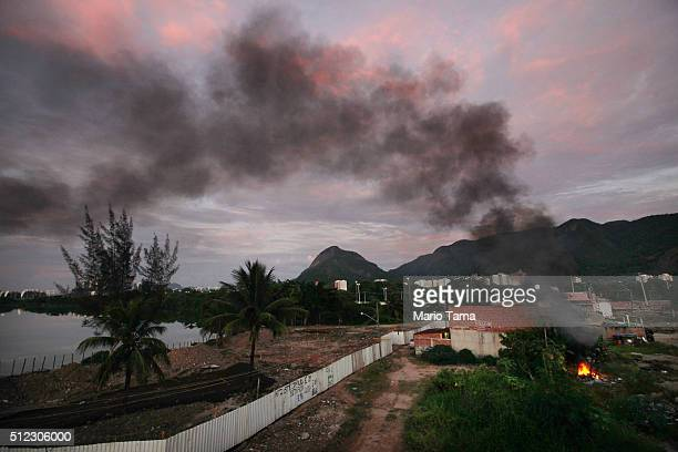 A small brush fire burns at dawn in the mostly demolished Vila Autodromo favela community a former fishing colony on February 25 2016 in Rio de...