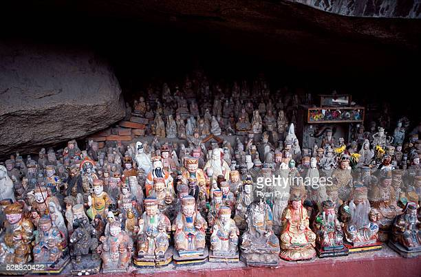 Small Buddha statues sit between two large rocks at the Nanputuo Temple in Xiamen. The Nanputuo Temple is located on the southeast of Xiamen Island....