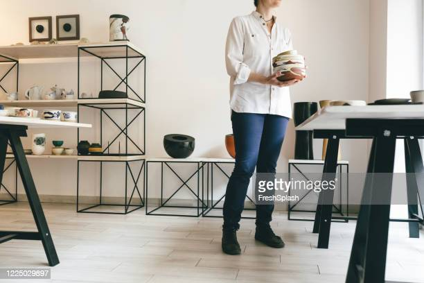 kleine unternehmen: eine frau handwerker holding gemalt terrakotta schalen im shop - kunsthändler stock-fotos und bilder