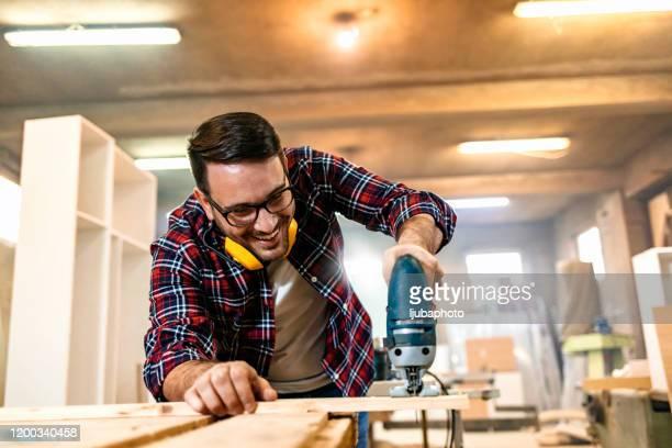 pequena empresa de um carpinteiro novo em sua loja de trabalho - pequeno - fotografias e filmes do acervo