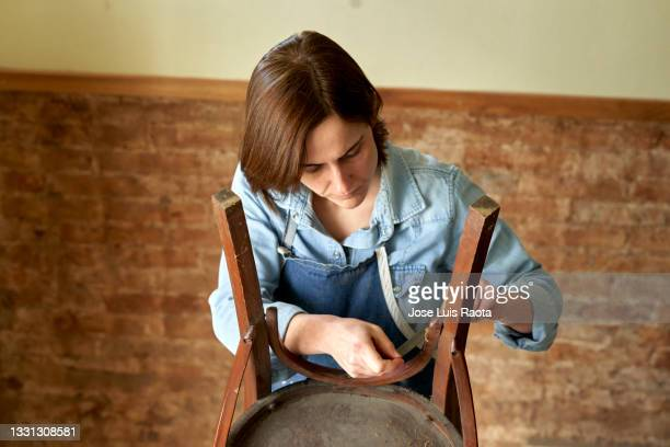 small business of a young woman.female worker restoring an old chair in a woodworking studio - chairperson stock pictures, royalty-free photos & images