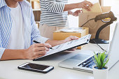 Small business owner delivery service and working packing box, business owner working checking order to confirm before sending customer in post office, Shipment Online Sales