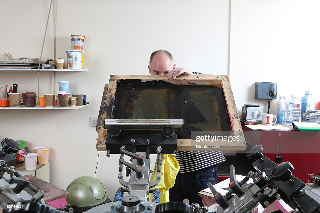 Small business owner doing Screen printing on t sh : Stock Photo
