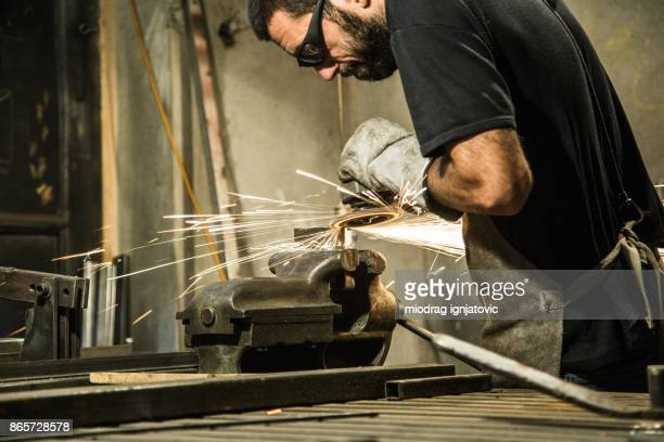 Small business owner grinding at his garage