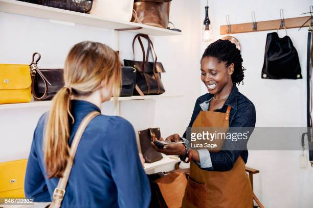 Small business owner happily conducting a sale in her store