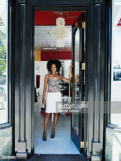 Small business owner holding open door of boutique