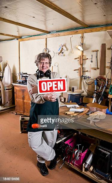 Small business owner, holding open sign