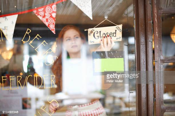 Small business owner in cafe turning closed sign