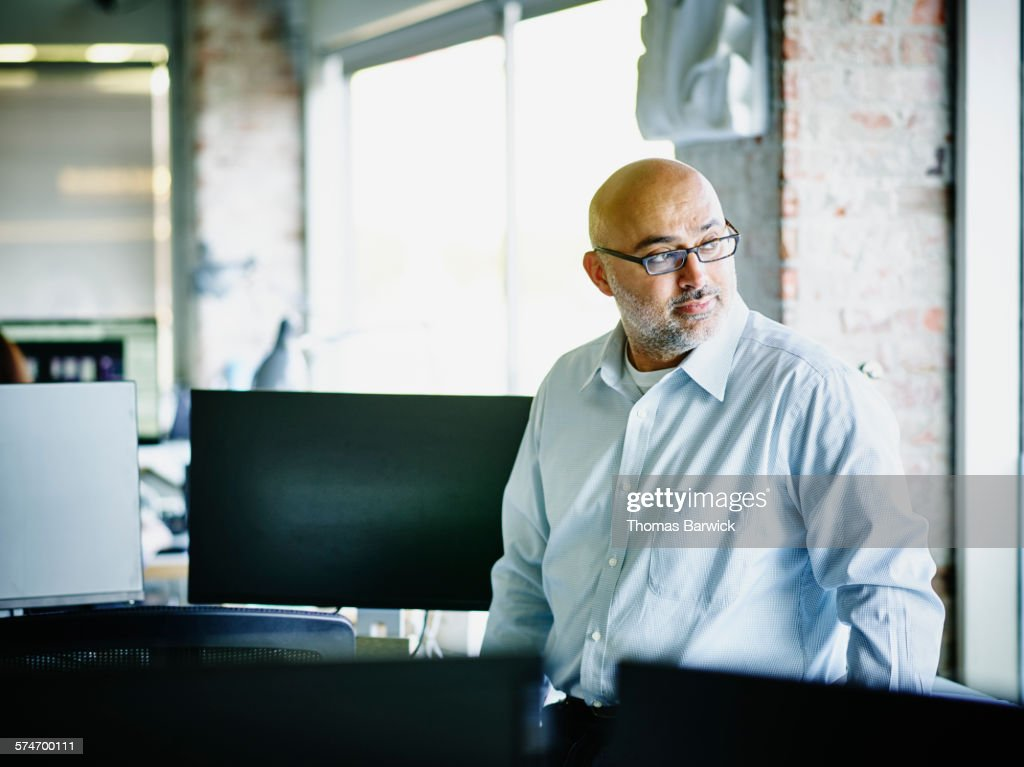 Small business owner looking out office window : Stock Photo