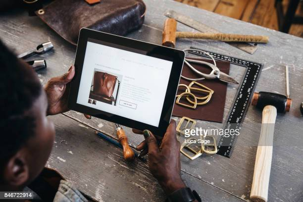 small business owner looks at her website on a digital tablet - web page stock pictures, royalty-free photos & images
