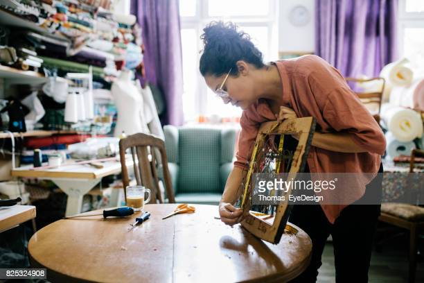 Small Business Owner Measuring Chair Seat In Workshop