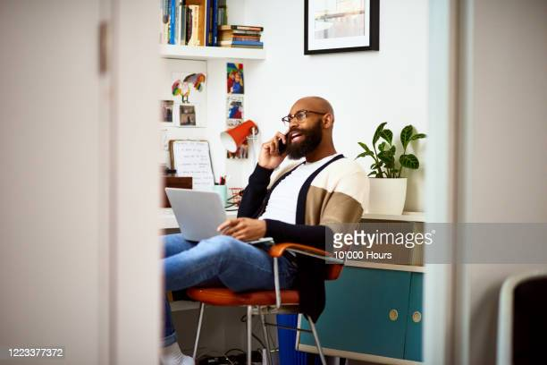 small business owner on phone at home - home office stock pictures, royalty-free photos & images