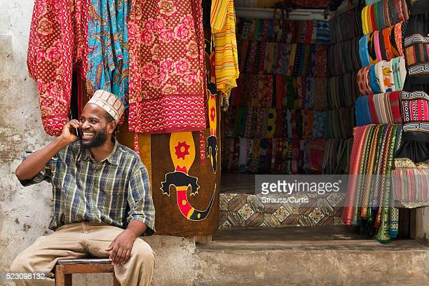 small business owner on phone in east african market - east africa stock pictures, royalty-free photos & images
