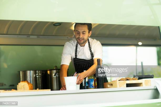 Small business owner preparing food in van food stall
