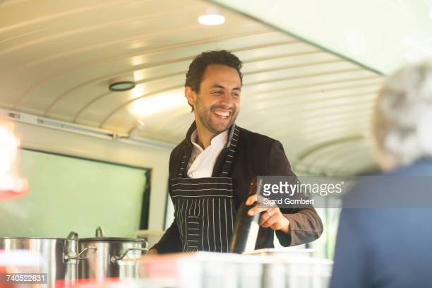 Small business owner serving customer at van food stall hatch