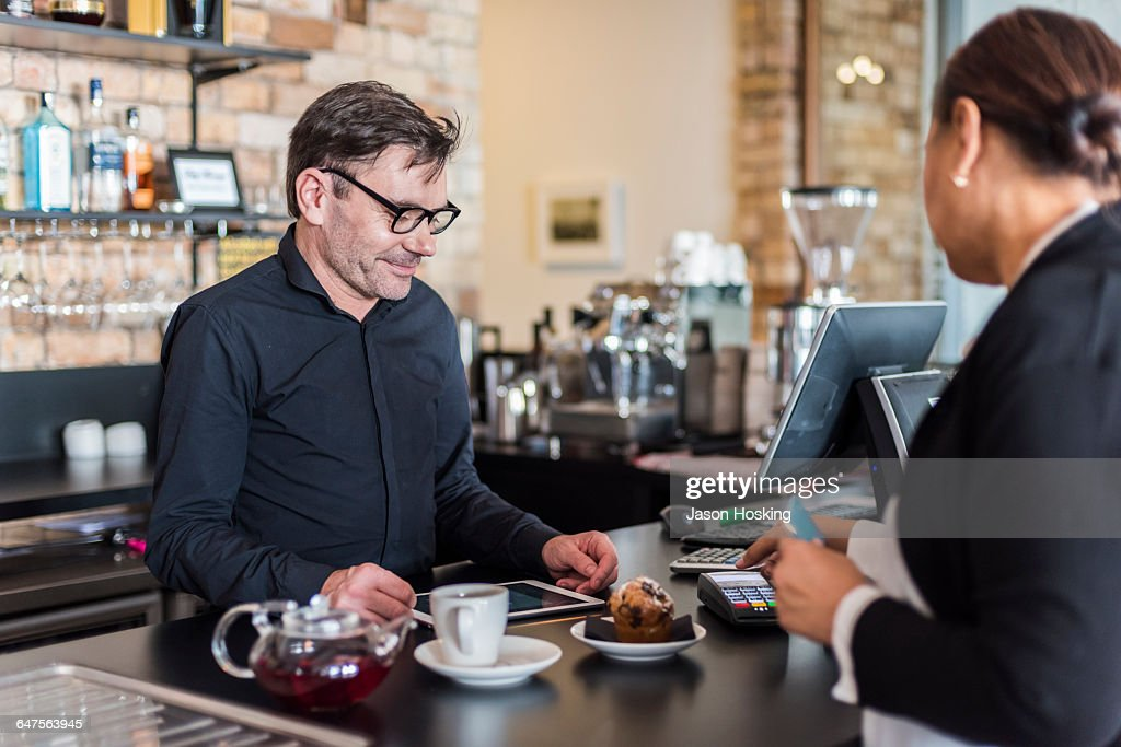 Small business owner serving customer : Stock Photo