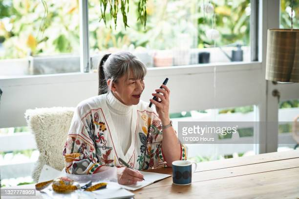 small business owner speaking on mobile phone and taking notes - greater london stock pictures, royalty-free photos & images