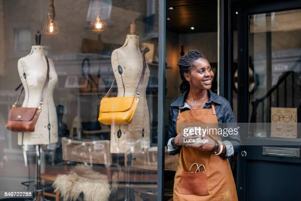a small business owner stands outside her handbag shop. - entrepreneur stock pictures, royalty-free photos & images