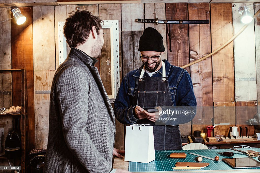 Small Business owner takes a customers payment : Stock Photo