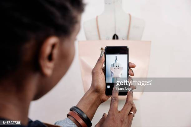 a small business owner takes a photo of her handmade leather bag, ready to upload to her website - hi tech moda stock pictures, royalty-free photos & images