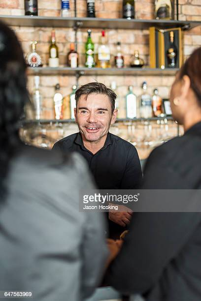 Small business owner talking to customers
